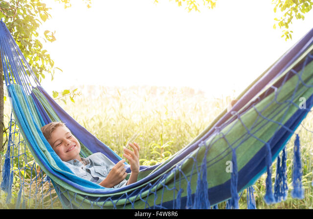 Carefree boy listening to music on mp3 player in rural hammock - Stock Image