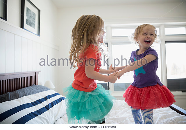 Playful sisters holding hands and jumping on bed - Stock Image