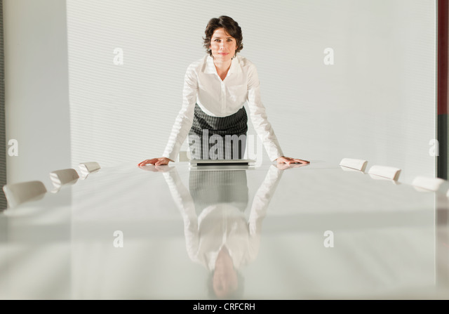Businesswoman reflected in table - Stock-Bilder