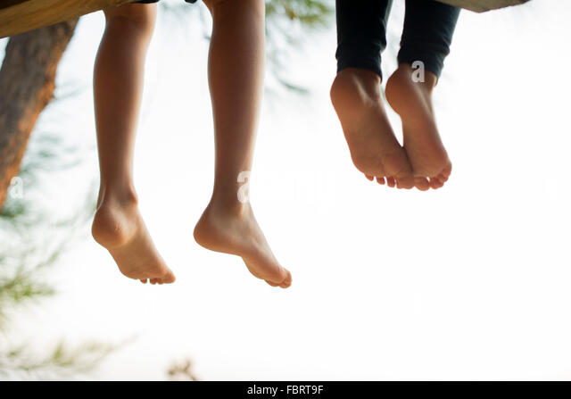 Barefoot children sitting side by side - Stock Image