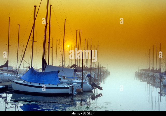 SUNRISE FOG OVER MARINA AND SAILBOATS ON WHITE BEAR LAKE, JUST NORTH OF ST. PAUL, MINNESOTA.  LATE SUMMER. - Stock Image