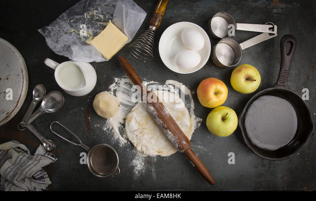 fresh dough with Ingredients for baking apple pie. Milk, eggs, butter, flour - Stock Image