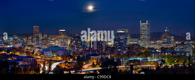 Moon Rise Over Portland Oregon City Skyline and Light Trails at Blue Hour - Stock Image