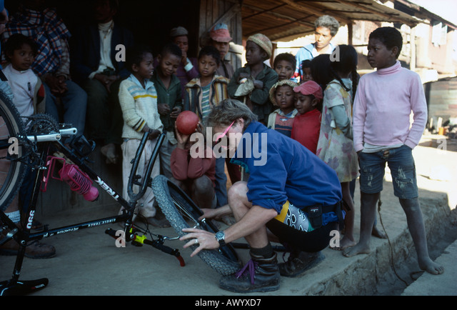 Sean O'Kelly mending a puncture on his mountain bike during the Tran-Madagascan Mountain Biking Expedition - Stock Image