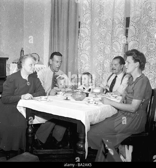 Family life in the 1950s England Different generations sit around the table having tea - Stock Image