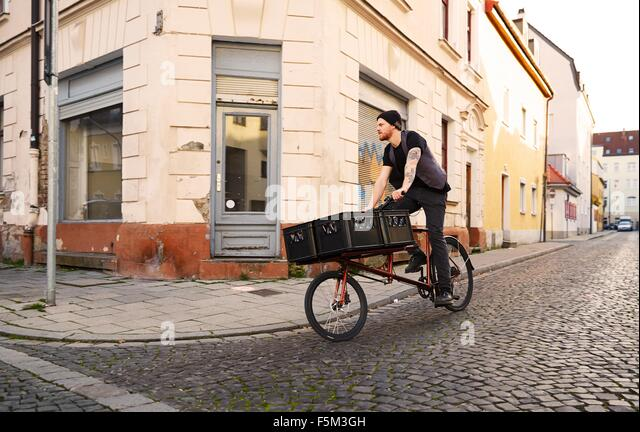 Man delivering beer on bicycle, Munich, Bavaria, Germany - Stock Image