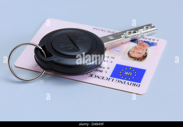 Remote car key with a woman's UK plastic card photographic driving licence on a plain blue background. - Stock Image