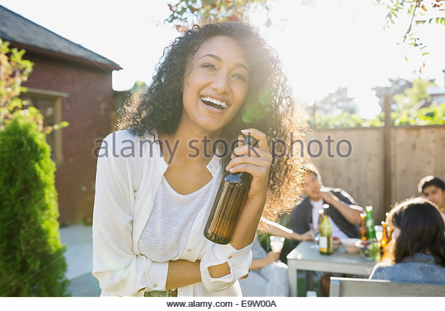 Laughing woman drinking beer at backyard barbecue - Stock Image