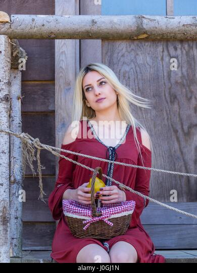Attractive beautiful blonde young woman basket fruit apple in hands - Stock Image