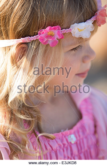 Profile of Young Girl Wearing Floral Headband - Stock Image