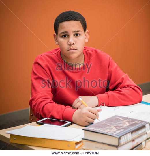 Serious teenage boy studying with textbooks - Stock-Bilder