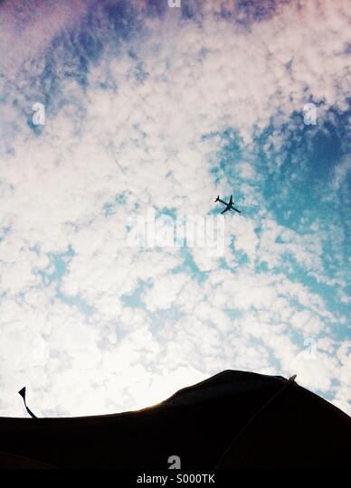 Upward view of a plane going by - Stock Image