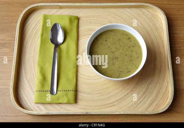 Tray with bowl of soup and spoon - Stock Image