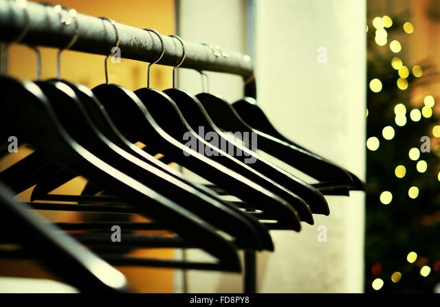 Coat Hangars On Metal Rod Against Defocused Christmas Lights In Office - Stock Image