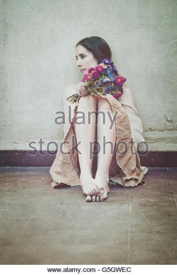 Young woman sitting on the patio holding flowers - Stock-Bilder