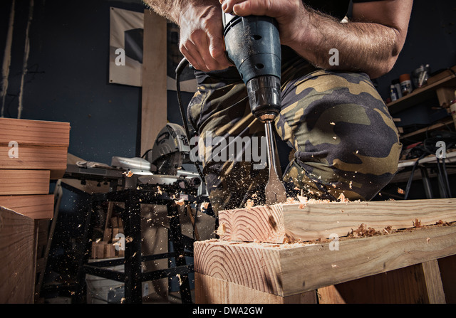 Close up of male carpenter drilling wooden plank in workshop - Stock Image