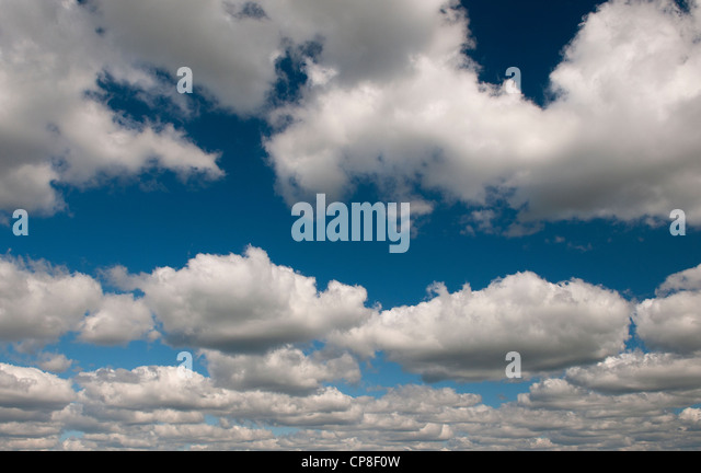 Top lit fluffy white clouds in a blue sky - Stock Image