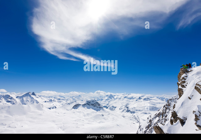 Three snowboarders look out over snowy mountain range, - Stock Image