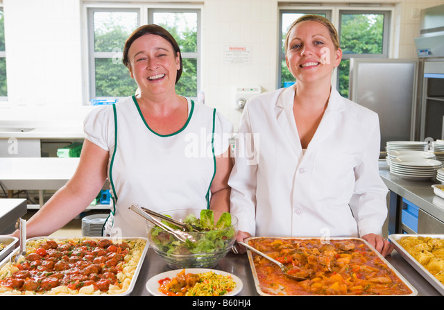 Two lunch ladies standing behind full lunch service station - Stock Image