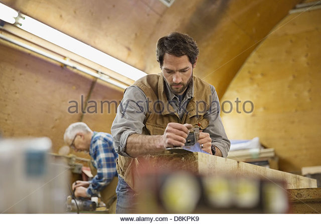 Woodworker using hand plane on lumber - Stock Image