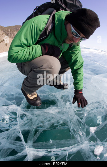 A hiker examines the frozen Lake Baikal during the winter in Siberia, Russia. - Stock Image