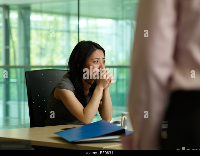 A woman looks at a crying girl - Stock Image