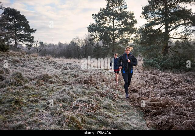 Front view of mother and son running on frosty grassland - Stock Image