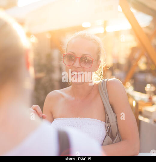Female friends enjoying a conversation on market. - Stock Image