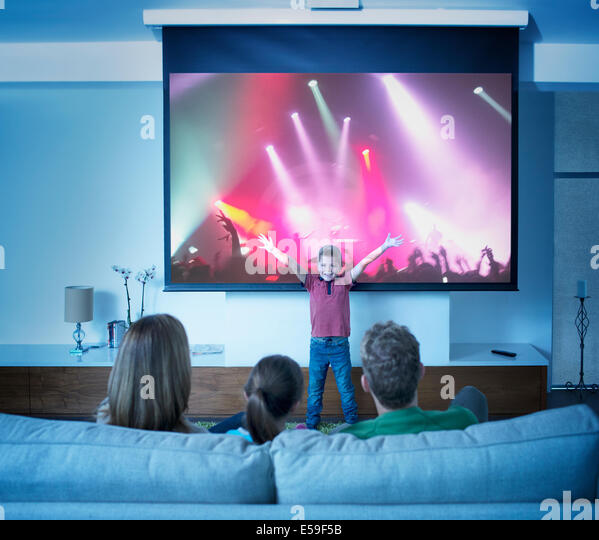 Family watching boy perform in front of concert screen - Stock Image