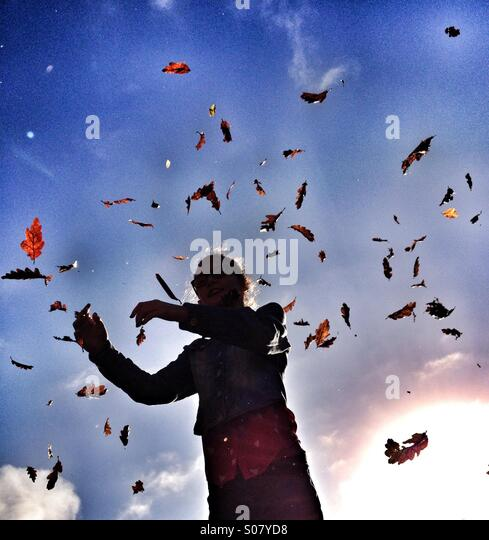 Young girl with autumn leaves falling around her - Stock Image