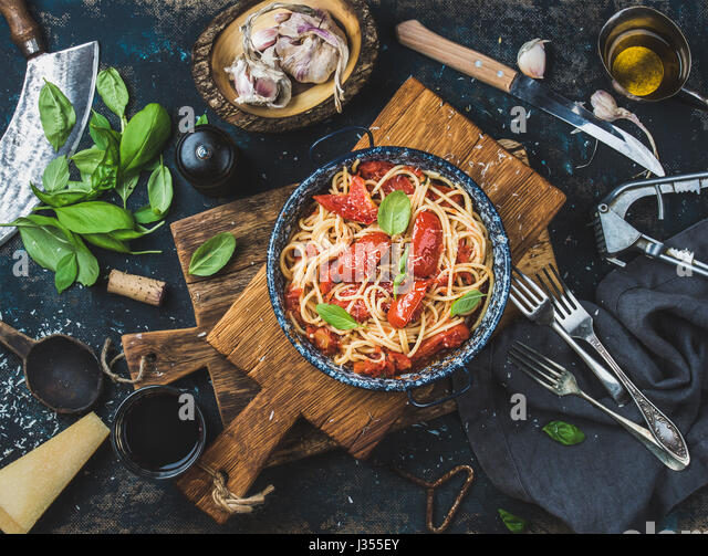 Spaghetti with tomato and basil in plate on wooden board - Stock Image