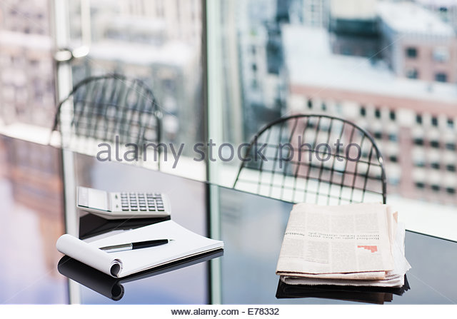 Desk with news paper, calculator and notepad - Stock Image