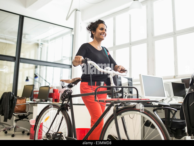 Smiling businesswoman with bicycle walking in creative office - Stock Image