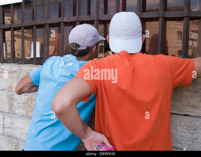 Two young men back view wearing baseball caps and t-shirts at a kiosk at the Arena, Arles, France - Stock Image