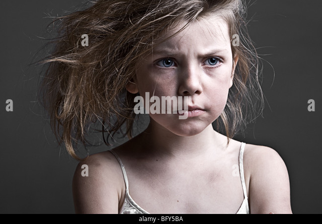 Powerful Shot of a Messy Child against a Grey Background - Stock Image