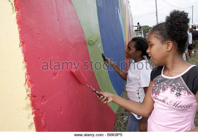 Miami Florida Hands on Miami Day volunteers community event painting mural Black girl girls student colorful wall - Stock Image