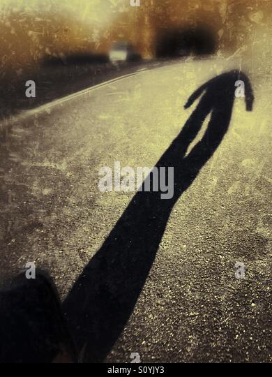 The long shadow of a man walking down a road. - Stock Image