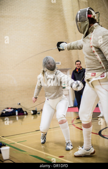 Two women Aberystwyth university students fencers competing at fencing, sabre style, UK - Stock Image