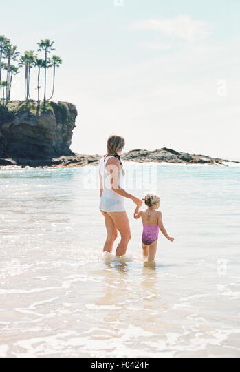 Woman playing with her daughter on the beach. - Stock Image