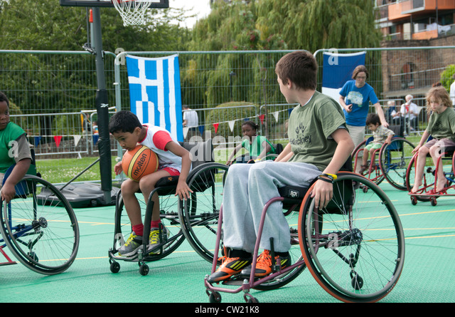 Haggerston Park Live Olympic screen. Able bodied children have the opportunity to play wheelchair basketball - Stock Image