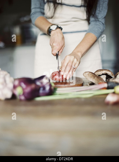 A domestic kitchen A table top Young woman chopping fresh vegetables with a knife - Stock-Bilder