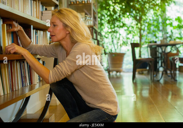 Mature woman looking at books on shelf at home - Stock Image