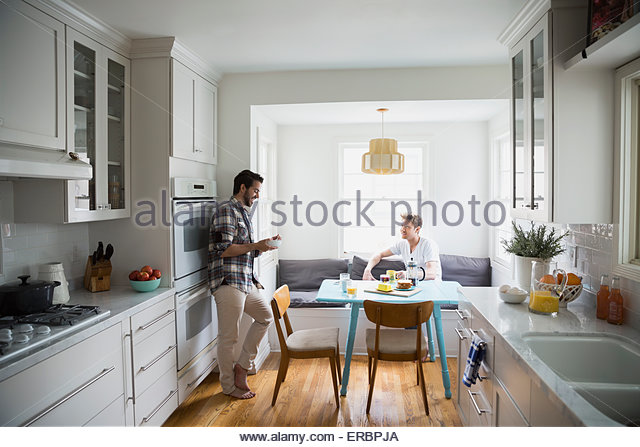 Homosexual couple talking and eating breakfast in kitchen - Stock Image