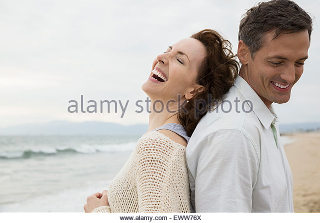 Carefree couple back to back on beach - Stock Image