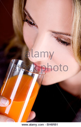 A mid adult woman drinking a glass of fruit/carrot juice - Stock Image