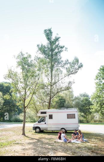 Group of young adults sitting on picnic blanket , relaxing, camper van in background - Stock Image
