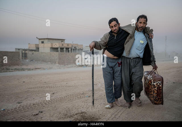 Mosul, Ninewa Province, IRAQ. 26th Nov, 2016. A man helps his injured friend make it to the field hospital at Gogjali - Stock Image