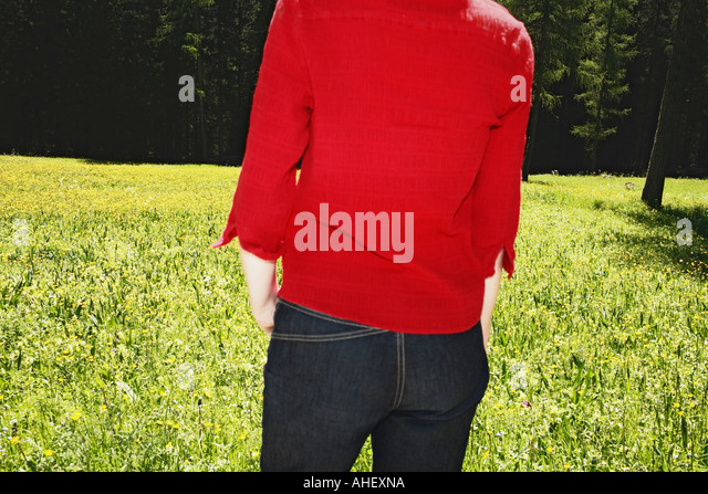 Young Woman In Red Shirt And Blue Denim Standing On Blooming Meadow Dolomites European Alps Italy - Stock Image