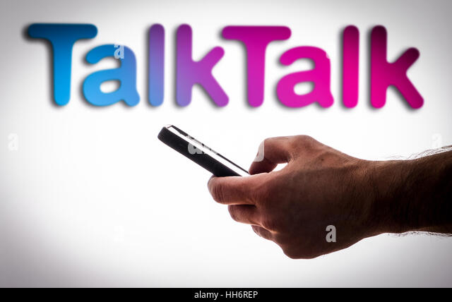 A man using a mobile phone in front of a TalkTalk logo - Stock Image