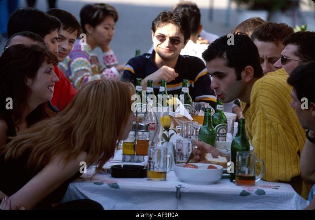 Greece Katakolon Ionian Sea coast fishing village alfresco dining young adults males females - Stock Image